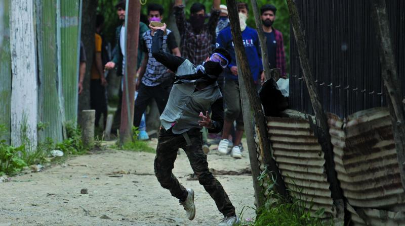 A youth throws stones at policemen during a protest on the outskirts of Srinagar on Monday. (Photo: AP)