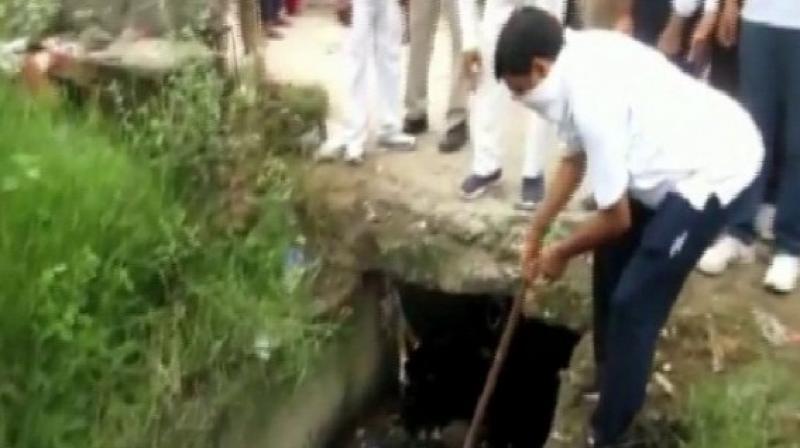 Rampur DM Anjaneya Kumar Singh engaged in cleaning a drain. (Photo: ANI)