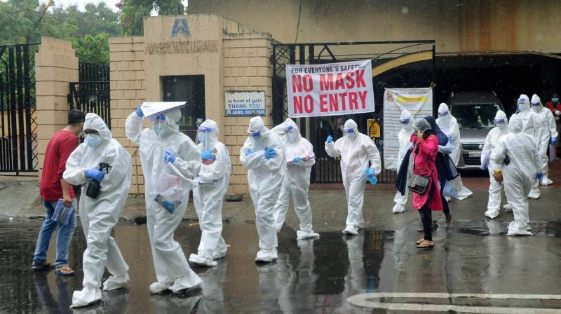 Health workers conduct door-to-door screening in the wake of coronavirus pandemic, during Unlock 2.0, at Evershine Nagar in Malad, Mumbai. PTI photo