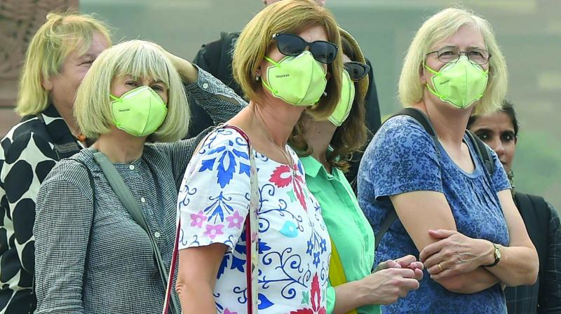 Tourists wear anti-pollution masks amid heavy smog in New Delhi. (Photo: PTI)