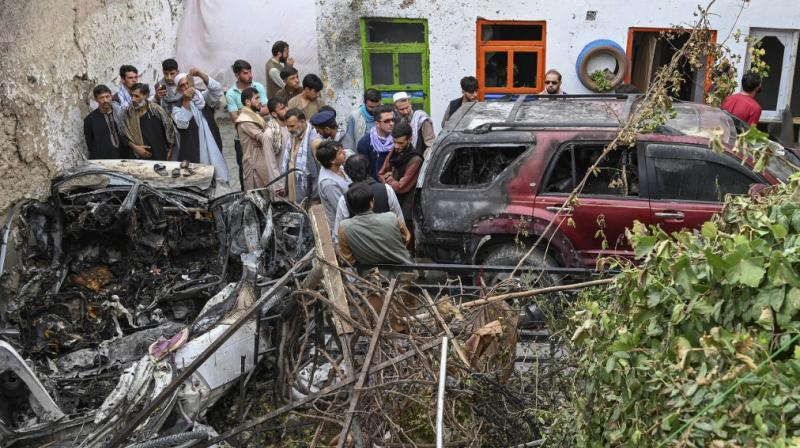 Afghan residents and family members of the victims gather next to a damaged vehicle inside a house, day after a US drone airstrike in Kabul. (AFP)