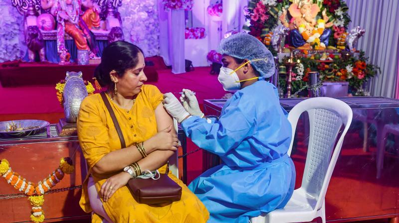 A health worker inoculates a woman with a dose of the Covishield coronavirus vaccine at a Ganpati pandal in Mumbai, Sept. 15, 2021. (PTI/Shashank Parade)