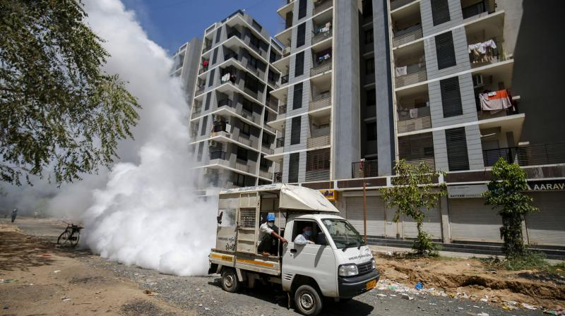Workers fumigate near a residential complex during a nationwide lockdown to limit the spreading of coronavirus, in Ahmedabad, on Sunday. PTI photo