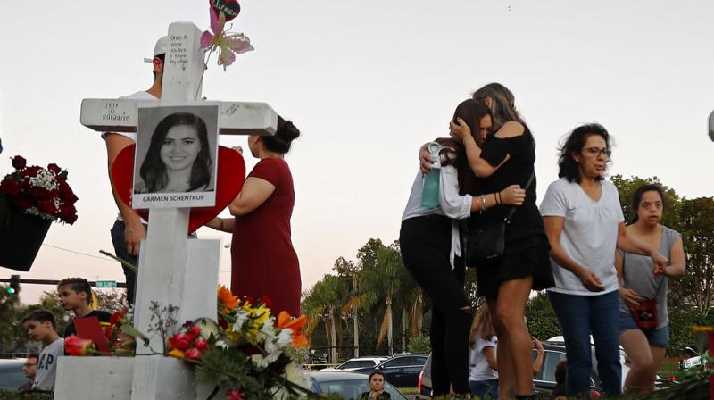 Magaly Newcomb, right comforts her daughter Haley Newcomb, 14, a student at Marjory Stoneman Douglas High School, at a makeshift memorial outside the school, in Parkland, Fla., Sunday, Feb. 18, 2018. Nikolas Cruz, a 19-year-old who had been expelled from the school, is being held without bail in the Broward County Jail, accused of 17 counts of first-degree murder. (Photo: AP)