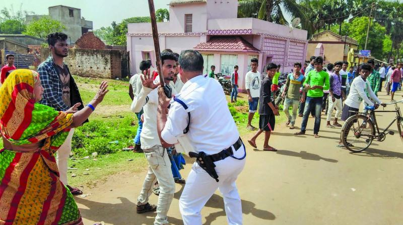 A policeman lathicharges a miscreant after a clash during the voting for the fourth phase of Lok Sabha elections in Durgapur, West Bengal, on Monday. (Photo: PTI)