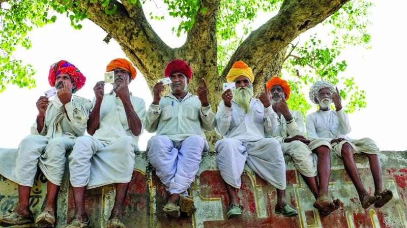 Voters show their voters identity cards and ink-marked fingers after casting their votes during the fourth phase of Lok Sabha elections in Ajmer on Monday. (Photo: PTI)