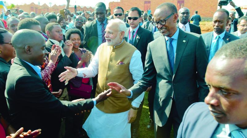 Prime Minister Narendra Modi, accomapanied by Rwandan President Paul Kagame, greets locals at the Rweru Model village on Tuesday. (Photo: AFP)