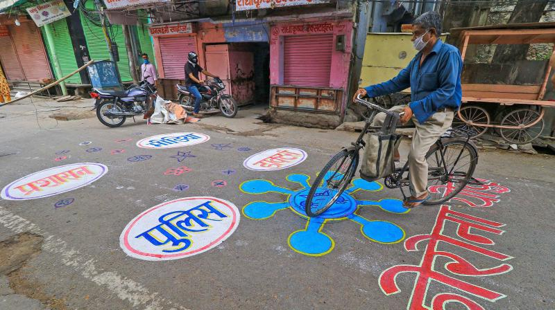 A man rides a bicyle on a grafitti painted on a street at a containment zone in the walled city of Jaipur. PTI photo