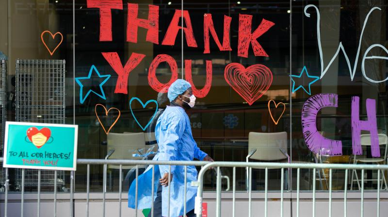 A Montefiore Medical Center employee walks past signs thanking the medical staff in New York. AFP photo