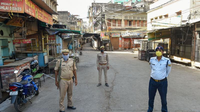 Police personnel stand guard in the Phoolbagh area sealed as one of the hotspots in UP. PTI photo