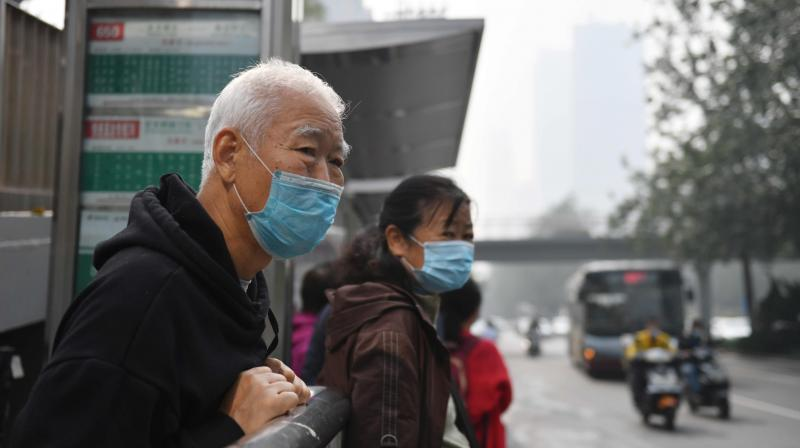 A man waits for a bus on a polluted day in Beijing. Qingdao has already locked down Qingdao Chest Hospital as well as the emergency department of its central hospital.  (AFP)