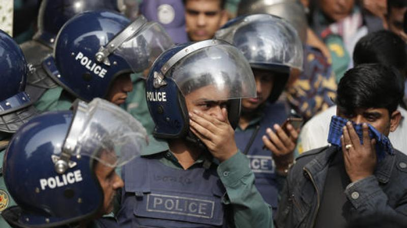 Bangladesh policemen cover their nose to protect themselves from the smell of teargas during a raid in a building in Dhaka, Bangladesh. (Photo: AP)