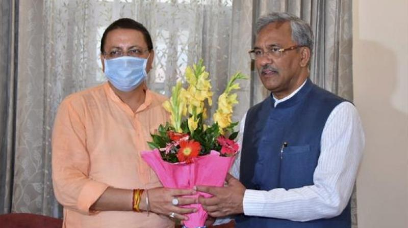 Uttarakhand CM designate Pushkar Singh Dhami with former chief minister TS Rawat, in Dehradun. (Photo: PTI)