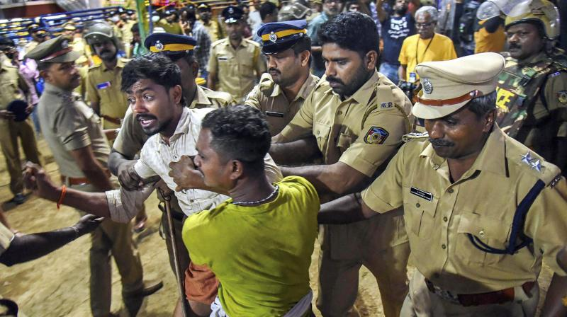 Police personnel detain the devotees who were staging 'Namajapa' protest against the police restrictions at Sannidhanam, in Sabarimala on Sunday. (Photo: PTI)