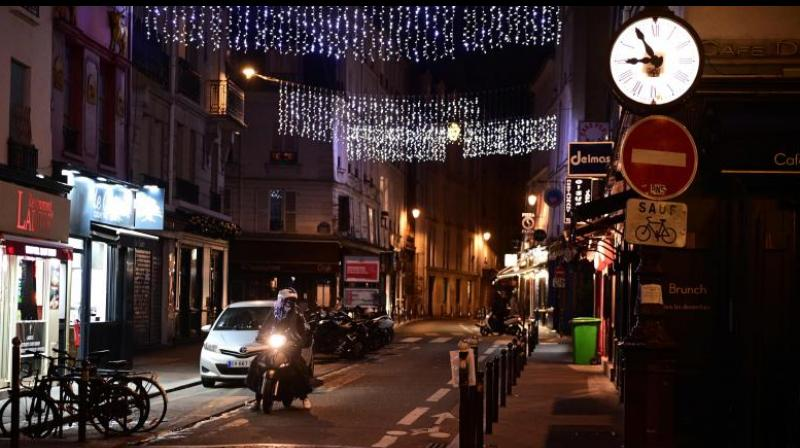 A motorcyclist rides on a deserted street in Paris on December 15, 2020, as a new 8:00 pm-6:00am curfew is implemented in France to avoid a third wave of coronavirus infections. The curfew will be waived for Christmas Eve in order to allow families to travel to celebrate together but it will be kept in place for New Year's Eve. (MARTIN BUREAU / AFP)