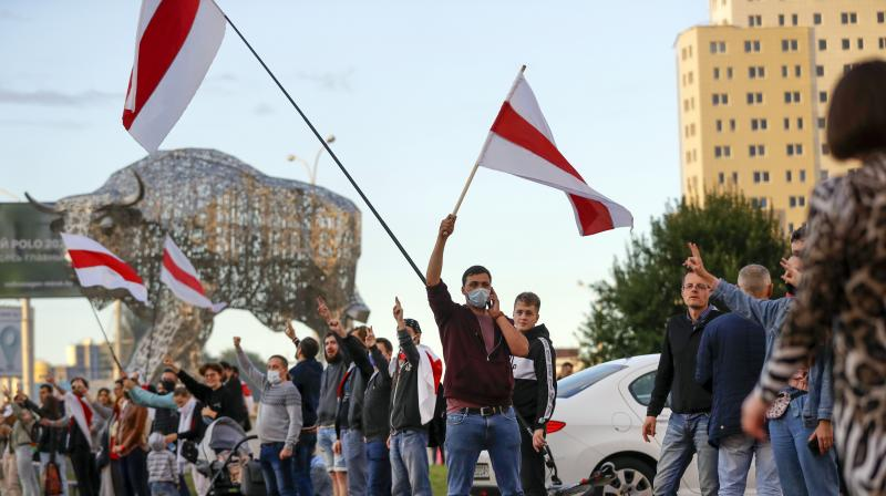 Protesters wave old Belarusian national flags standing along a street in Minsk, Belarus. (AP)