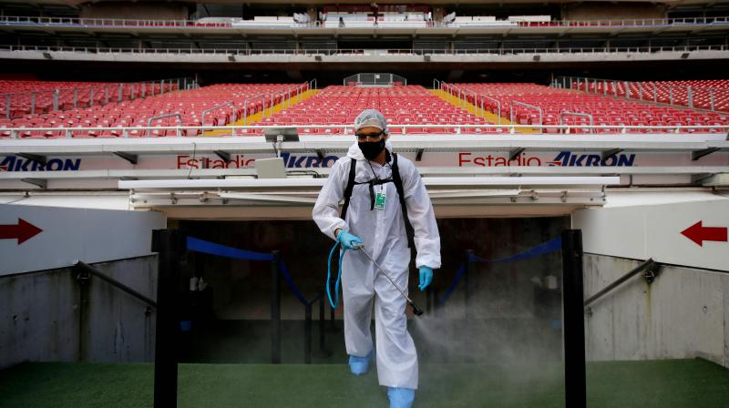 A Guadalajara staff member disinfects the stands before the start of a Mexican Apertura tournament football match between Guadalajara and Pachuca in Guadalajara, Jalisco state, Mexico. (AFP)
