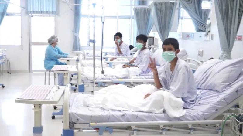 Footage shows them behind quarantine glass in bed wearing smocks and facemasks, flashing peace signs and doing the traditional 'wai' greeting. (Photo: AP)