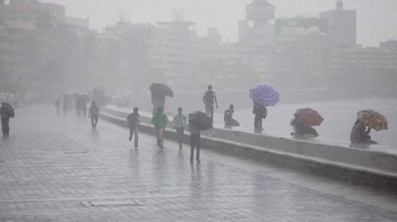People walk in heavy rains at Marine Drive in Mumbai on Wednesday. (Photo: AP)