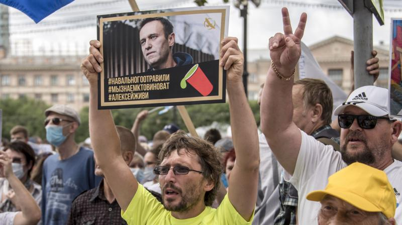 A man holds a poster with a portrait of Alexei Navalny reading