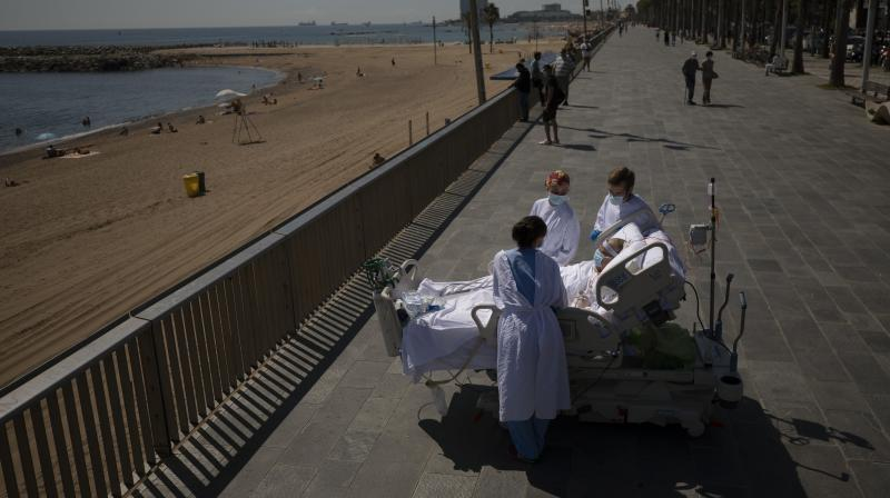 Francisco Espaata, 60, is surrounded by members of his medical team as he looks at the Mediterranean sea from a promenade next to the