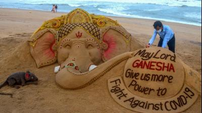 "Sand artist Sudarsan Pattnaik creates a sand sculpture on the occasion of Ganesh Chaturthi with message ""May Lord Ganesha give us more power to fight against COVID-19"", at Puri beach in Odisha. (PTI)"