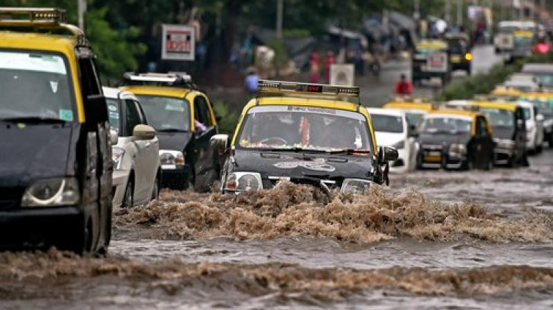 Vehicles wade through a water logged street after heavy rain in Mumbai on Wednesday. (Photo: PTI)