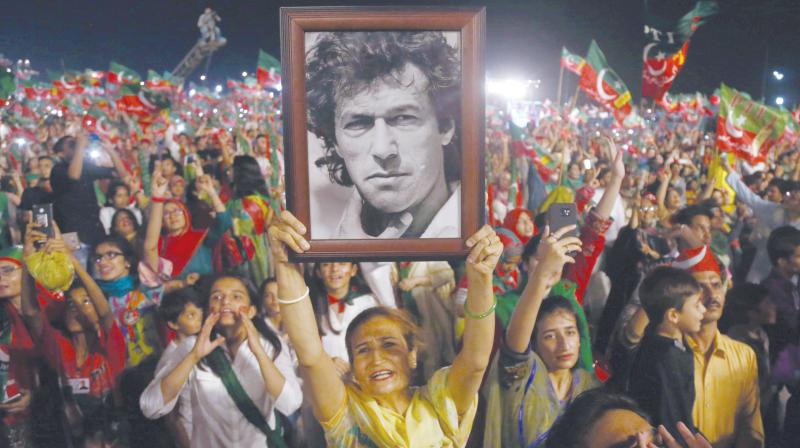 Supporters hold Imran Khan's picture in Karachi. (Photo: AP)