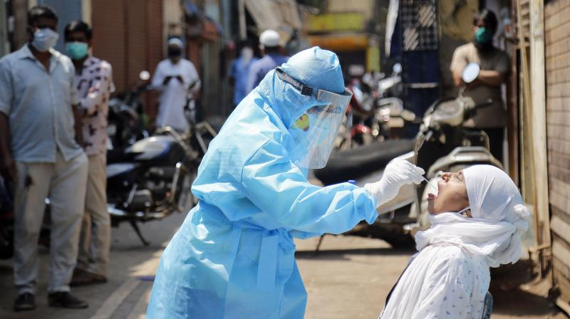 A medic collects swab from the mouth of a woman resident for COVID-19 test in a containment zone at Kurla, Mumbai. PTI photo