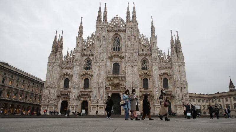 Women wearing face masks walks past the Duomo gothic cathedral in Milan, Italy. AP photo