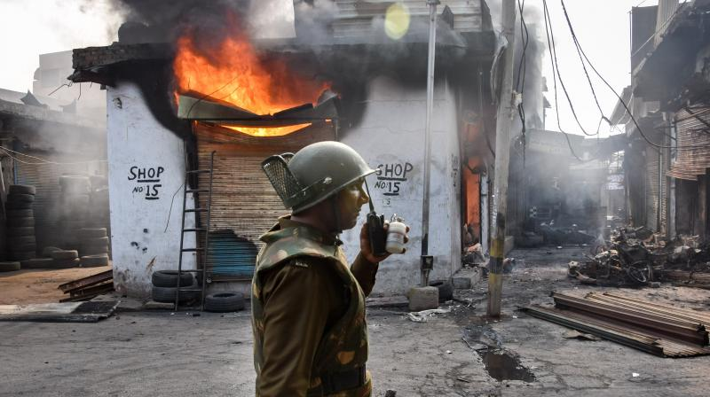 A security official stands in front of a burning shop following clashes over the new citizenship law, in Gokulpuri area of northeast Delhi on Wednesday. (PTI photo)