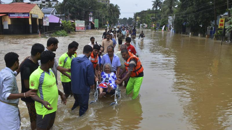 An elderly woman is evacuated towards safer area in Thrissur. (Photo: PTI)