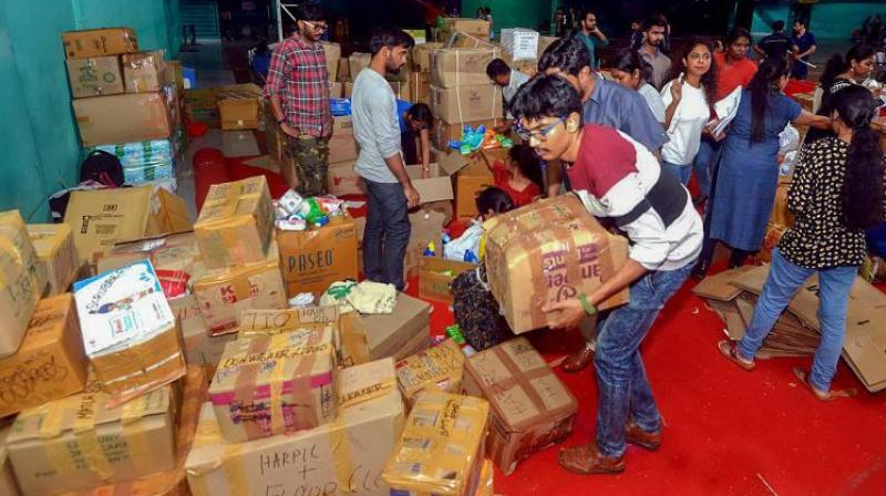 Anbodu Kochi volunteers and District Civil officers organise relief material to be sent to flood affected areas in Kochi. (Photo: PTI)