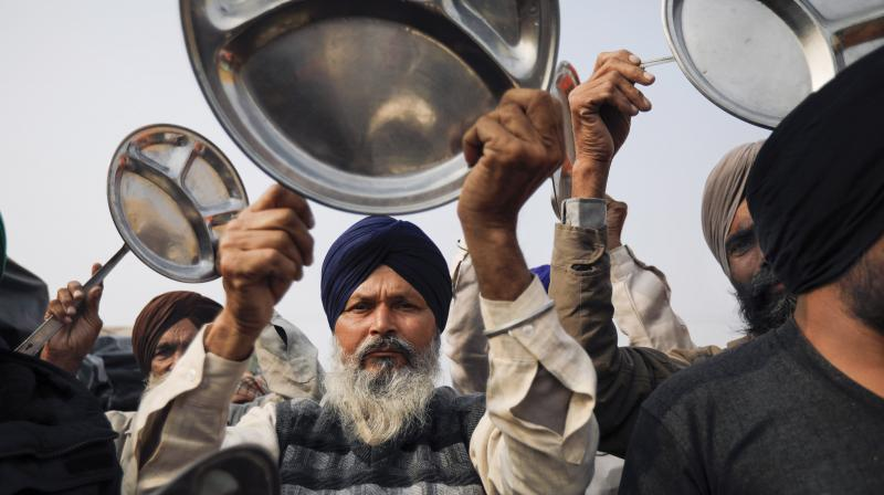 Farmers beat utensils as a protest against PM Modi's Man ki Baat programme, during their ongoing agitation over new farm laws, at Singhu border in New Delhi, Sunday, Dec. 27, 2020. (PTI)