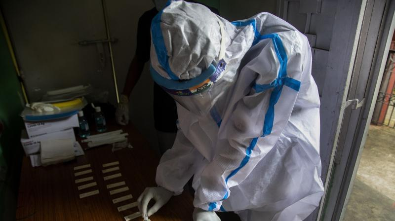 A health worker tests nasal swab samples for COVID-19 in Gauhati, India. (AP)