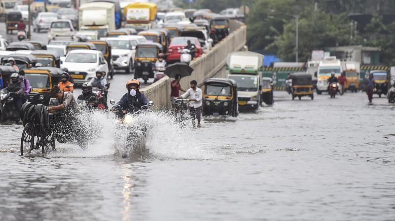 Commuters wade through a waterlogged street as heavy rain continues at Santacruz- Chembur Link Road, in Mumbai. (PTI)
