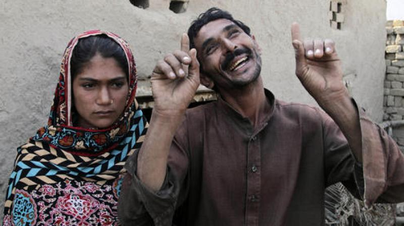 Mohammad Ramzan, right, reacts while talking to his young bride Saima in Jampur, Pakistan. (Photo: AP)