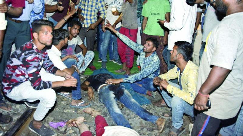 An angry crowd shout slogans as they sit by bodies of victims of the train accident in Amritsar on Friday. (Photo: AP)