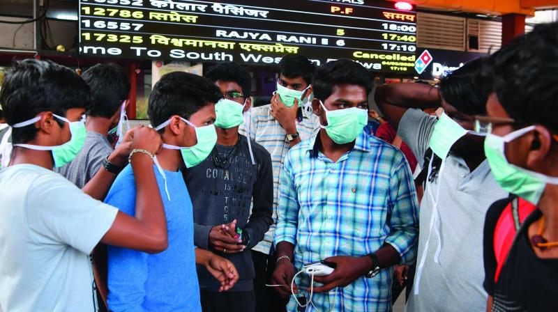 Tourists wear facemasks as a preventive measure against the spread of the COVID-19 coronavirus outbreak at the Bangalore City Railway Station on Wednesday. (Photo: PTI)