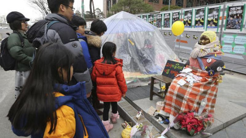 People watch a statue symbolizing women forced into wartime Japanese military brothels in front of the Japanese Embassy in Seoul, South Korea. (Photo: AP)