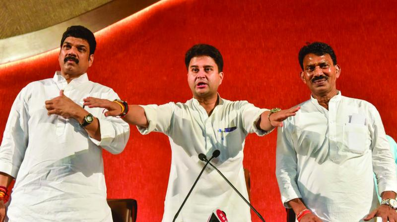 Senior Congress leader Jyotiraditya Scindia, along with Cabinet ministers Govind Rajput and Tulsi Silawat, before addressing a press conference during ongoing monsoon session of the state Assembly in Bhopal on Thursday. (Photo: PTI)