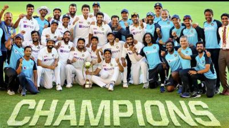ndian players pose with the winning trophy after defeating Australia by three wickets on the final day of the fourth cricket test match at the Gabba, Brisbane, Australia, on Tuesday. -- PTI