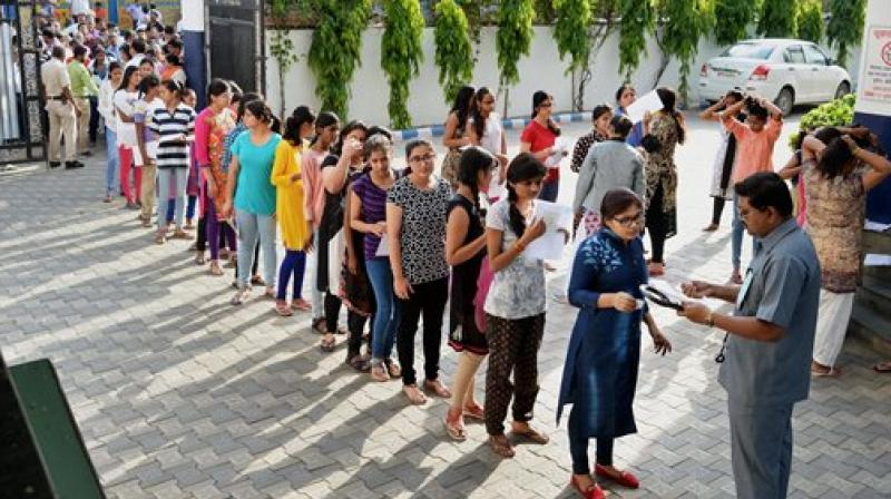 Candidates being checked before appearing for the NEET exam on Sunday. (Photo: AP)