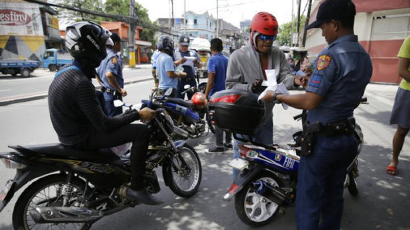 Policemen inspect motorcycle riders at a checkpoint in Manila, Philippines, Wednesday, May, as the Philippine National Police is placed under full alert status following the declaration of martial law in Mindanao southern Philippines. (Photo: AP)