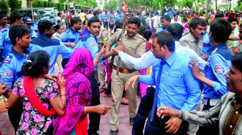 Police and private security personnel clash with domestic helps and local villagers who gathered at a housing society in Noida on Wednesday to protest after a maid was allegedly beaten by her employers on suspicion of theft. (Photo: PTI)