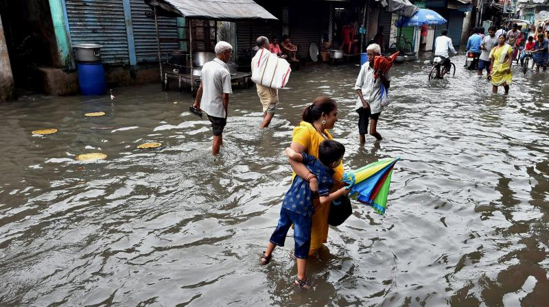 People wade through a waterlogged street after heavy rains in Kolkata on Sunday. (Photo: PTI)