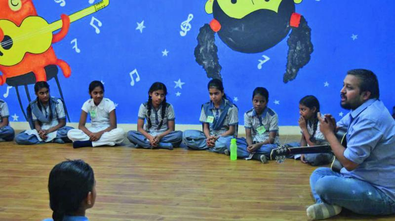 CEO of Manzil, Anurag Hoon interacting with children and teaching them music.