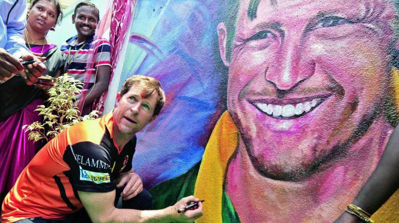 Jonty Rhodes signs an autograph on a painting during his visit to a Chennai school. (Photo: Asian Age)