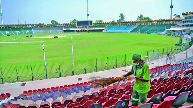 Workers clean Lahore's Gaddafi Stadium, which has witnessed both history and controversy — and is now preparing to retake the world stage. (Photo: AFP)