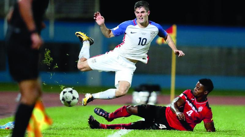 Christian Pulisic (top) of the US reacts after being fouled by Kevon Villaroel of Trinidad and Tobago. (Photo: AP)